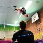Trampolin springen mit Unterstützung durch einen Trainer
